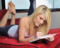 Schönes blondes Frauenschreiben im Journal Lizenzfreie Stockfotos