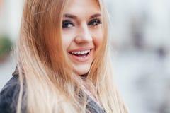 Schönes blondes Gesicht, das draußen in der Straße lacht Lizenzfreie Stockfotografie