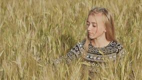 Schönes blondes jugendlich Mädchen, das auf einem Weizengebiet und -c$lächeln sitzt stock video footage