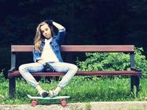 Schönes blondes jugendlich Mädchen im Jeanshemd, sitzend auf Bank mit Rucksack und Skateboard im Park Stockbild