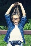 Schönes blondes jugendlich Mädchen im Jeanshemd, sitzend auf Bank mit Rucksack und Skateboard im Park Stockfotos