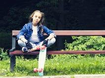 Schönes blondes jugendlich Mädchen im Jeanshemd, sitzend auf Bank mit Rucksack und Skateboard im Park Stockbilder