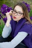 Schönes blondes jugendlich mit Gläsern, violettes Kleid Lizenzfreie Stockfotografie
