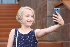 Schönes blondes jugendliches Mädchen, das ein Telefon, ein Selbstporträt mit Handy nehmend verwendet Stockfoto