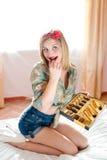 Schönes blondes junge Frau Pinupmädchen, das Praline isst u. Kamera auf sonnigem Fensterhintergrund betrachtet stockfotografie