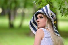 Schönes blondes junges lächelndes Frauenporträt in den grünen Vorderteilen Stockfoto