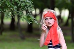 Schönes blondes junges lächelndes Frauenporträt in den grünen Vorderteilen Lizenzfreie Stockfotografie