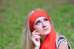 Schönes blondes junges lächelndes Frauenporträt in den grünen Vorderteilen Stockbilder