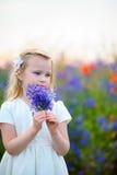 Schönes blondes junges Mädchen auf grünem Feld mit Blumen Stockbilder
