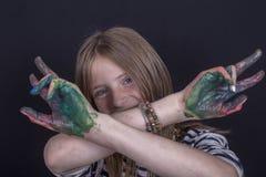 Schönes blondes junges Mädchen mit den Sommersprossen und Händen zuhause gemalt in den bunten Farben auf schwarzem Hintergrund, N Stockfotos