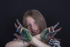 Schönes blondes junges Mädchen mit den Sommersprossen und Händen zuhause gemalt in den bunten Farben auf schwarzem Hintergrund, N Lizenzfreie Stockfotografie