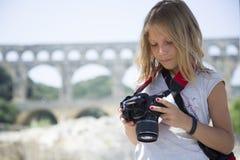 Schönes blondes junges Mädchen mit Kamera Lizenzfreies Stockfoto