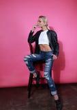 Schönes blondes junges Modell, das in der schwarzen Lederjacke und in b aufwirft Lizenzfreies Stockbild