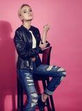 Schönes blondes junges Modell, das in der schwarzen Lederjacke und in b aufwirft Lizenzfreie Stockbilder