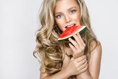 Schönes blondes junges Modell, nettes Mädchen, Wassermelone halten und schauen nett Stockbilder