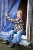 Schönes blondes Kind, das auf Fensterbrett sitzt Lizenzfreie Stockfotografie