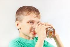 Schönes blondes Kind, das frische Limonade trinkt Lizenzfreies Stockfoto