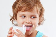 Schönes blondes Kind, das frische Milch auf weißem Hintergrund trinkt Stockfotos