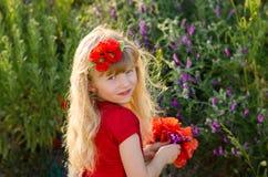 Schönes blondes Kind mit Blumen Lizenzfreie Stockfotos
