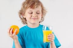 Schönes blondes Kind mit einem Glas eines frischen Safts und der Orange Stockbilder