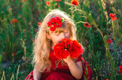 Schönes blondes Kind mit Mohnblumenblumen Lizenzfreies Stockbild