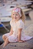 Schönes blondes Kindermädchenporträt auf Seeseite mit Booten auf Hintergrund Stockbild