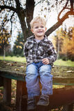 Schönes blondes Kindersitzen im Freien auf Tabelle Herbst Lizenzfreies Stockbild