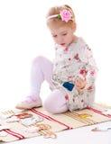 Schönes blondes kleines Mädchen, das auf der Wolldecke sitzt und Stockbild