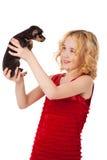 Schönes blondes kleines Mädchen, das den Welpen trägt rotes Kleid hält Lizenzfreie Stockbilder