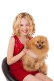 Schönes blondes kleines Mädchen, das ihren Hund trägt rotes Kleid hält Lizenzfreie Stockbilder