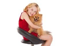 Schönes blondes kleines Mädchen, das ihren Hund trägt rotes Kleid hält Lizenzfreies Stockfoto
