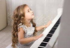 Schönes blondes kleines Mädchen, das Klavier spielt Stockfotografie