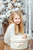 Schönes blondes kleines Mädchen, das unter dem Weihnachtsbaumesprit sitzt lizenzfreie stockfotografie