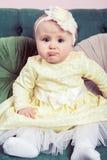 Schönes blondes kleines Mädchen mit gelbem Kleid und Blume auf ihrem Kopf Stockbild