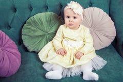 Schönes blondes kleines Mädchen mit gelbem Kleid und Blume auf ihrem Kopf Stockbilder