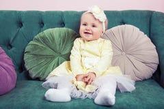 Schönes blondes kleines Mädchen mit gelbem Kleid und Blume auf ihrem Kopf Lizenzfreies Stockfoto