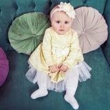 Schönes blondes kleines Mädchen mit gelbem Kleid und Blume auf ihrem Kopf Stockfoto