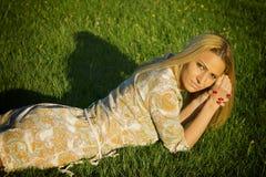Schönes blondes Lügen auf dem Gras Lizenzfreie Stockfotografie
