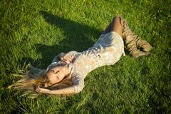 Schönes blondes Lügen auf dem Gras Stockfotos