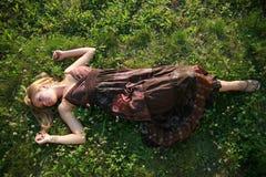 Schönes blondes Lügen auf dem Gras Lizenzfreies Stockbild