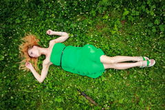 Schönes blondes Lügen auf dem Gras, unten oben schauend, hunds, Spitze Stockfoto