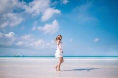 Schönes blondes langes Haarfrauentanzen auf dem Strand Glücklicher Insellebensstil Weißer Sand, blauer bewölkter Himmel und Krist Stockfotos