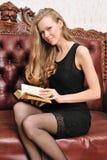 Schönes blondes Lesebuch auf dem antiken Sofa. Lizenzfreie Stockbilder