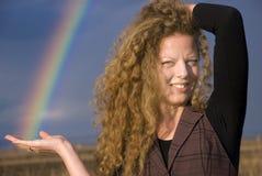 Schönes blondes lockiges Mädchen, das einen Regenbogen anhält Stockfoto