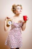 Schönes blondes lustiges Pinupmädchen mit den Lockenwicklern, die den goldenen Wecker u. Schale des heißen Getränks Kameraporträt Stockbild