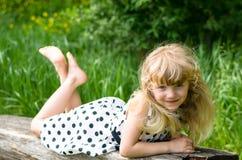 Schönes blondes Mädchen auf Bank Stockfotos
