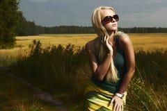 Schönes blondes Mädchen auf dem field.beauty woman.sunglasses stockfotografie