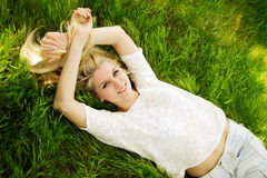 Schönes blondes Mädchen auf dem grünen Gebiet Stockbild