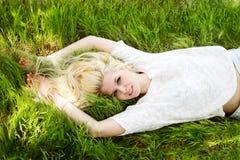 Schönes blondes Mädchen auf dem grünen Gebiet Stockbilder