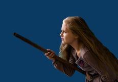 Schönes blondes Mädchen auf einem Besenstiel in Form von Hexenblauhintergrund stockfotografie